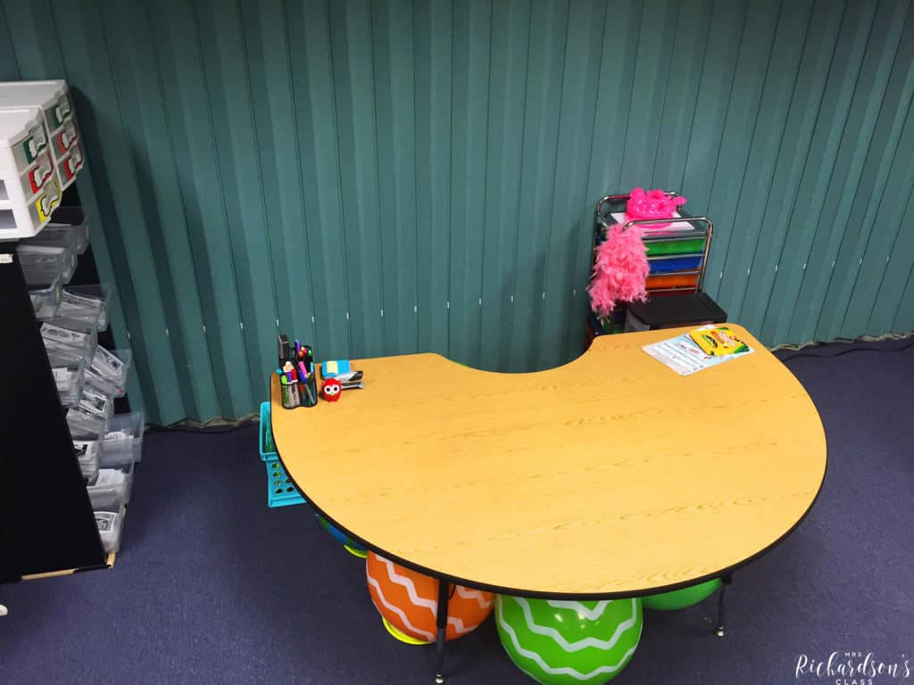 This teacher guided reading table is organized so nicely! She has supplies on the right in a tall tower and books on a shelf to the left. Student sit on yoga balls, which are housed on small rings to keep them from rolling when not in use.
